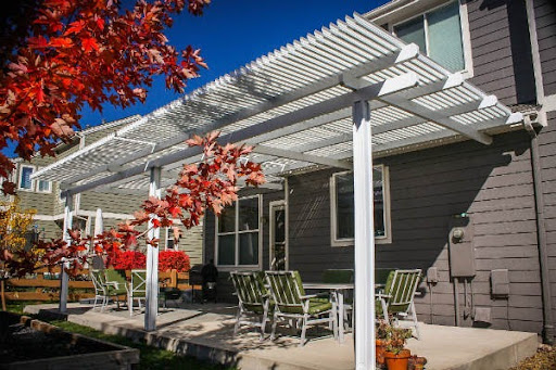 Image of a white Cardinal Motorized Pergola shading a backyard patio with table and chairs.